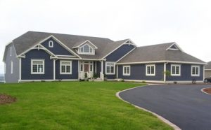 Beautiful blue house with multiple roof peaks and wide trims
