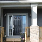Front entrance of house with black door and two posts with rock work - new home construction