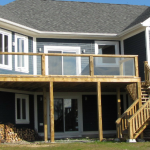 A large deck on the back of a two story blue house - new home construction