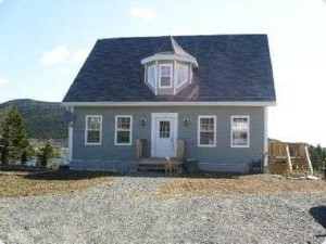 Grey Cape Cod style house with dog at front step