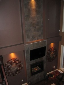 Fireplace with tile work extending toward ceiling