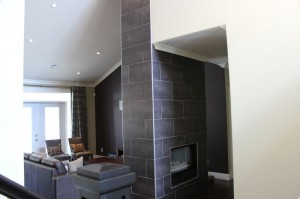Living room with double sided fireplace with tile work