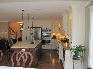 Kitchen with white cabinets and brown accented centre island